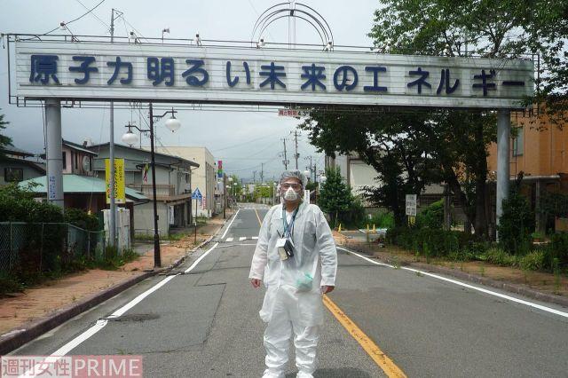 2011年8月、2回目の一時帰宅で双葉町に入った大沼勇治さん。当時、看板はまだ撤去されていなかった=本人提供