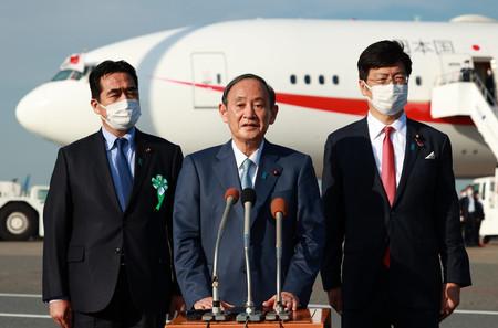 日米豪印首脳会議への出発前に、取材に応じる菅義偉首相(中央)=23日午後、羽田空港